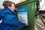 NABU-Meeresschutzexperte Kim Detloff kennzeichnet einen Sammelcontainer. Fischer können darin kostenlos Abfälle entsorgen, der sich in ihren Netzen verfangen haben.